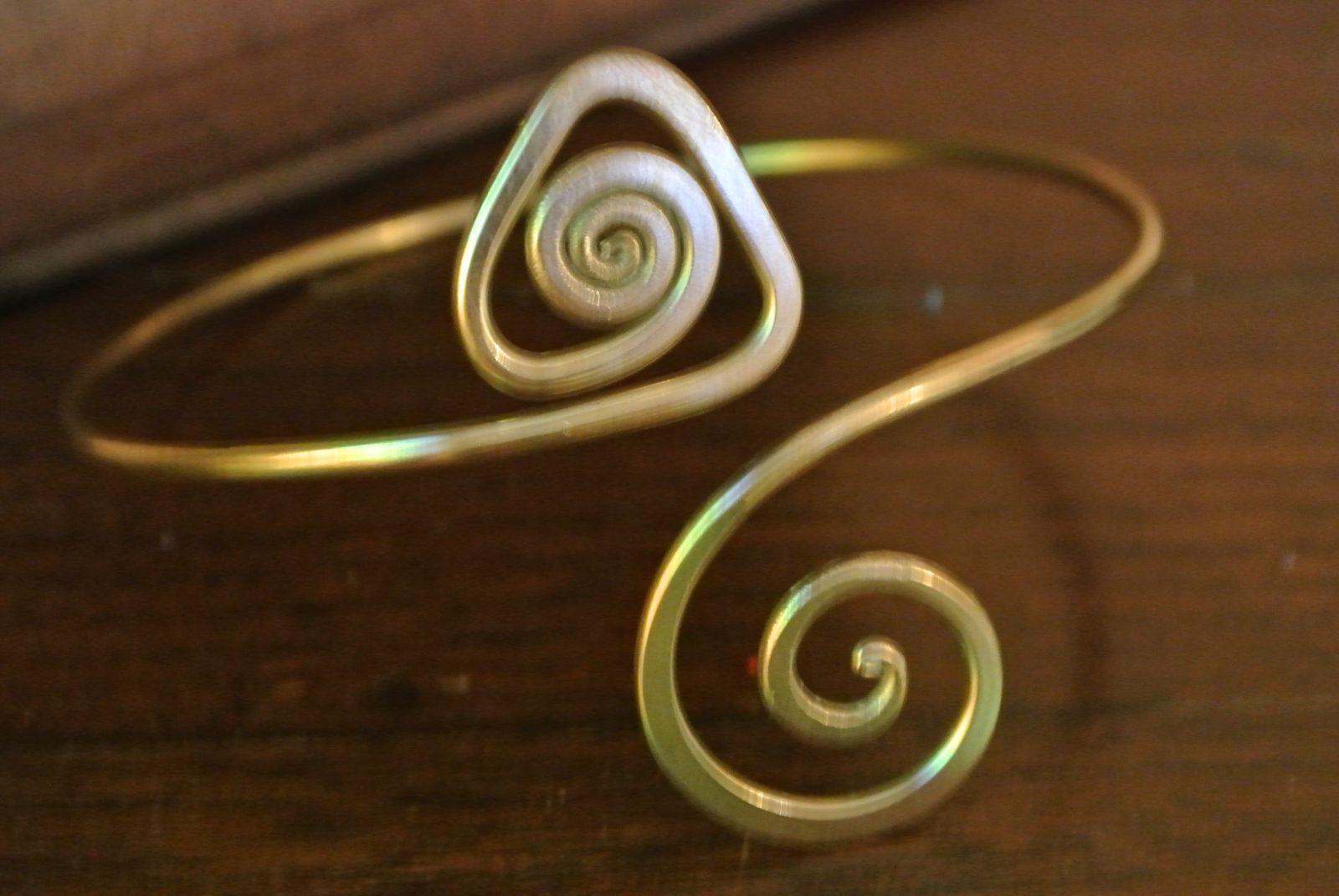bracelet  laqué en doré porté en haut du bras